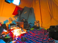 In the tent at night, cozy as can be. Pulk Tank in front of the stove and the kettle on the go as always. Candles and lanterns blazing, dinner in a pot, life is good!